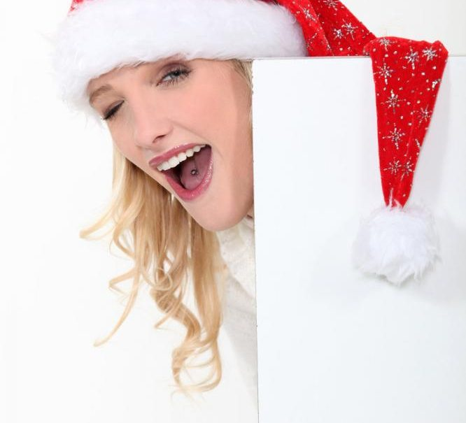 Woman with a tongue piercing wearing Santa's hat